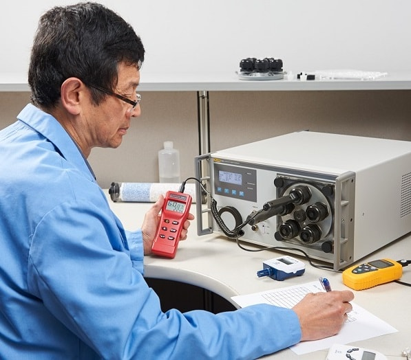 Calibration Technician Calibrating Humidity Sensors with a Humidity Generator Calibrator